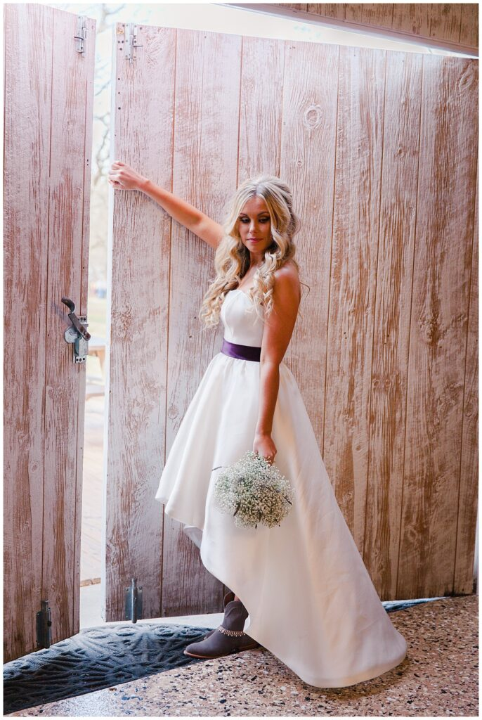 Texas bride poses in front of barn door for outdoor Texas styled wedding at Fort Worth Country Memorial Wedding Venue photographed by Dallas wedding photographer Jenny Bui of Picture Bouquet Studio.