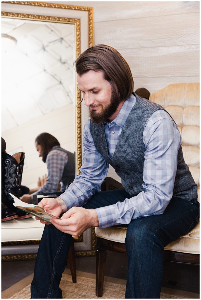 Groom reading letter from bride as he is getting ready for outdoor Texas styled wedding at Fort Worth Country Memorial Wedding Venue photographed by Dallas wedding photographer Jenny Bui of Picture Bouquet Studio.