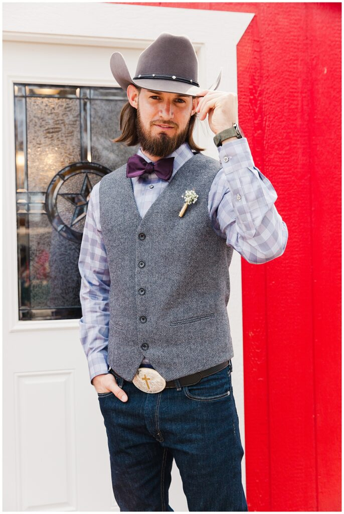 Groom poses in cowboy hat and purple bowtie for outdoor Texas styled wedding at Fort Worth Country Memorial Wedding Venue photographed by Dallas wedding photographer Jenny Bui of Picture Bouquet Studio.
