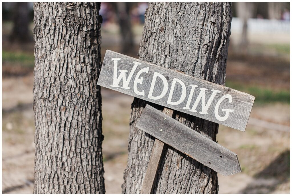 Wedding arrow sign for outdoor Texas styled wedding at Fort Worth Country Memorial Wedding Venue photographed by Dallas wedding photographer Jenny Bui of Picture Bouquet Studio.
